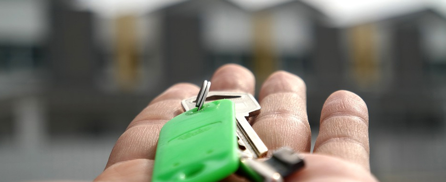 hand holding out a pair of keys with blurry houses in the background for buying a new home